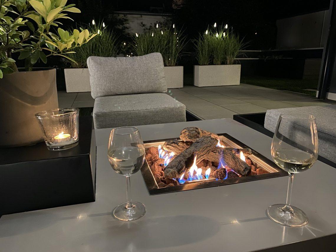 Feuertisch am Abend mit Weingläsern