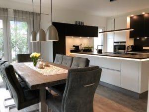 Esstisch mit moderner Küche und Hintergrundbeleuchtung